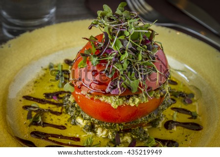 Fresh tomato tower appetizer filled with olive tapenade sitting on ricotta cheese, balsamic vinegar and olive oil and garnished with microgreens sitting on rustic yellow plate - stock photo