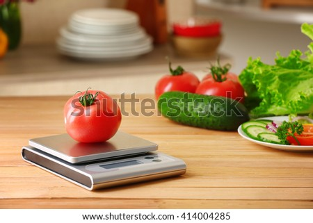 Fresh tomato with digital kitchen scales on wooden table - stock photo