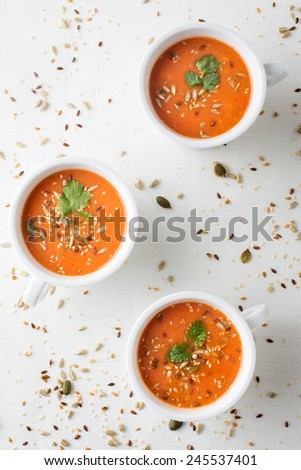 fresh tomatoe soup in cups with seeds and parsley. Vertical image. - stock photo