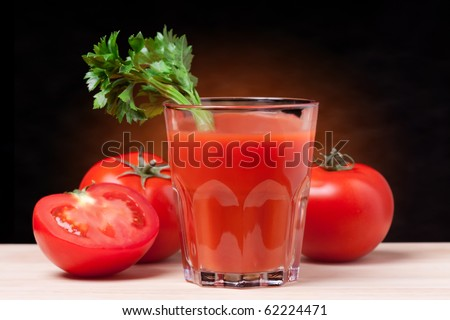Fresh tomatoes and a glass full of tomato juice. - stock photo