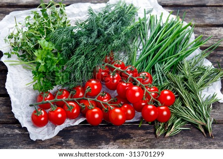 Fresh Tomatoes and Green Vegetables.  Dill, Rosemary, Parsley, Chives and thyme. on old wooden table. - stock photo