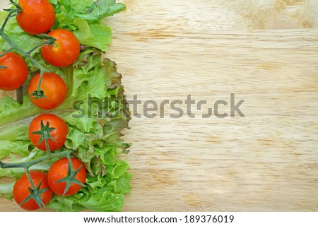 Fresh tomatoes and lettuce on wooden background