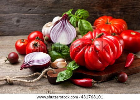 fresh tomatoes, basil, red onion, garlic and black pepper on the old wooden background - stock photo