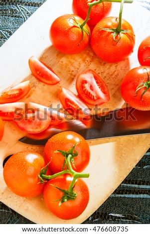Fresh tomatoes being prepared into a tomato wedge salad on a glass table.