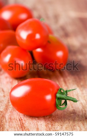 fresh tomatoes bunch closeup on wooden table - stock photo