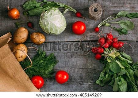 Fresh tomatoes, cabbage, radish, potato, onion and dill on wooden table, top view - stock photo