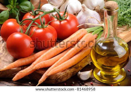 Fresh tomatoes, carrot and olive oil on the wooden cutting board - stock photo