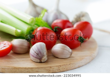 Fresh tomatoes, garlic and stems of celery on cutting board on white wooden background - stock photo