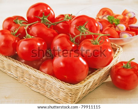 Fresh tomatoes in a wicker basket on table and a plate with salad