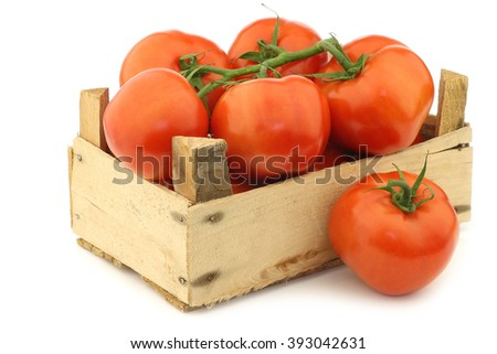 fresh tomatoes in a wooden crate on a white background