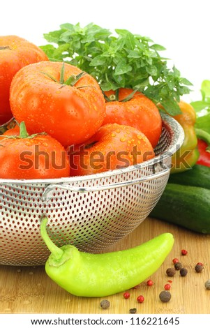 Fresh tomatoes in metal colander - stock photo