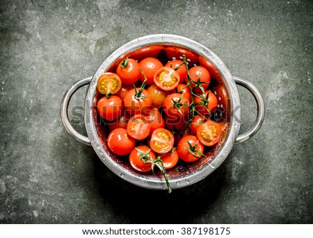 Fresh tomatoes in the bowl. Wet stone background.  - stock photo