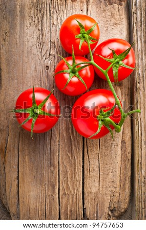 Fresh tomatoes on vintage wooden table - stock photo