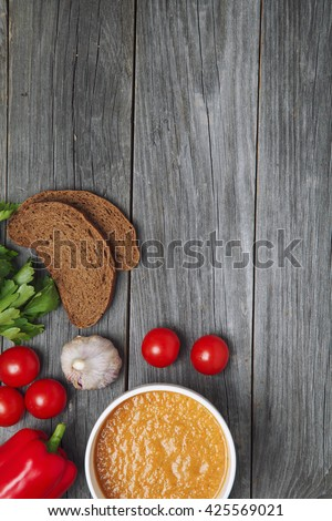 Fresh tomatoes soup with vegetables on a wooden table.  Viewed from above. Empty space for text - stock photo
