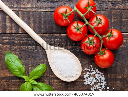Fresh tomatoes with basil and spoon with salt on grunge wooden board