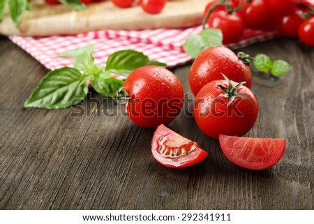 Fresh tomatoes with basil on wooden table close up - stock photo