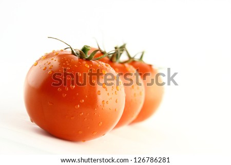 fresh tomatoes with green leaves on white background