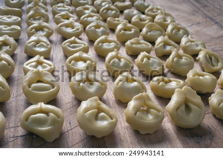 fresh tortellini on a wooden board, a typical food of Italian cuisine - stock photo