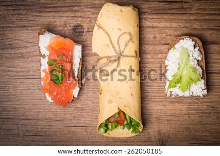 fresh tortilla wrap with vegetables and two sandwiches on wooden background top view - stock photo