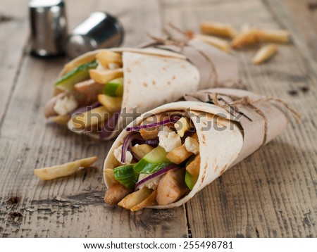 Fresh tortilla wraps with grilled chicken,vegetables and potato, selective focus