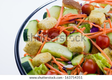 Fresh tossed garden salad set against a white background. - stock photo