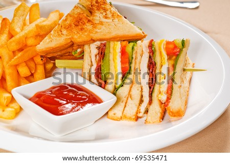 fresh triple decker club sandwich with french fries on side - stock photo
