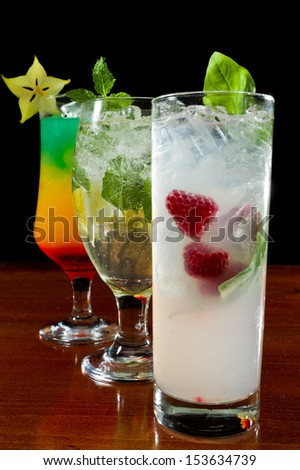 fresh tropical cocktails served on a bar with a black background
