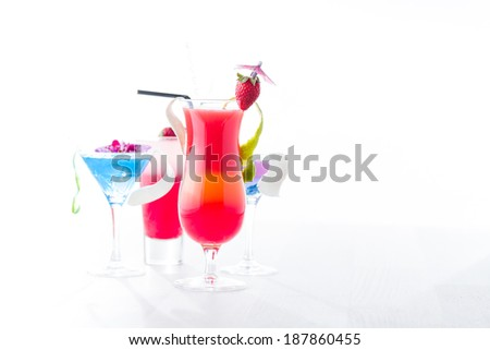 Fresh tropical layered cocktails over white background - stock photo