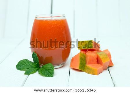 Fresh tropical papaya juice isolated on a white wooden background. - stock photo
