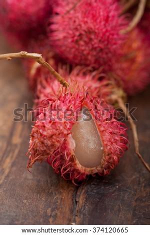 fresh tropical rambutan fruits over rustic wood table  - stock photo