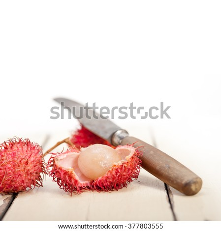 fresh tropical rambutan fruits over rustic wood table