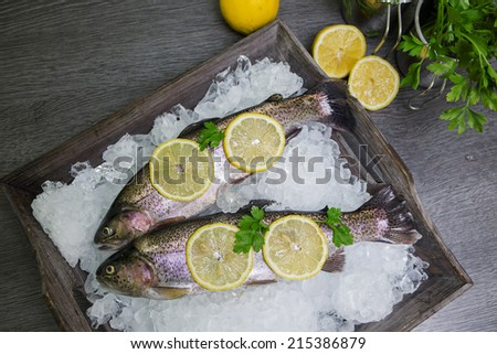 Fresh trout with lemon on a wooden tray - stock photo