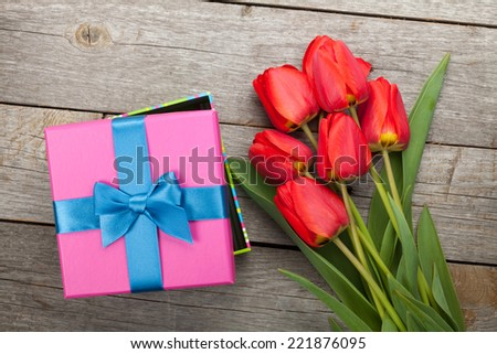 Fresh tulips and gift box over wooden table background - stock photo