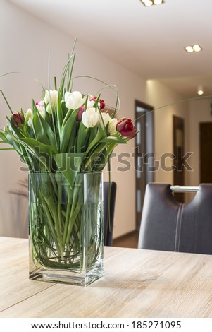 Fresh tulips flowers on the dinning table in modern interior - stock photo