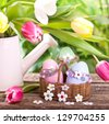 fresh tulips with colorful self designed easter eggs in a basket on wooden table - stock photo