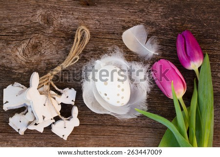 fresh tulips with easter egg in feather nest and bunnies on wooden table, top view - stock photo