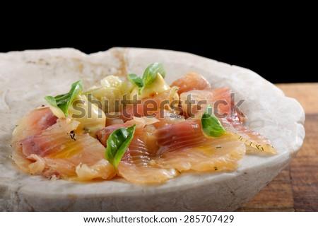 Fresh Tuna carpaccio with basil, radish, onion and olive oil - stock photo