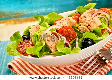 Fresh tuna salad served in a white oval dish with lettuce, olives, onion and tomato on a wooden table near a beach or pool in summer sunshine - stock photo
