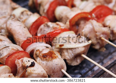 fresh turkey pink brisket shish kebab on wooden skewers with tomatoes over barbecue brazier full burned charcoal - stock photo