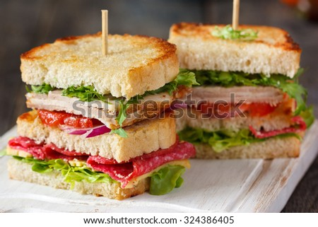Fresh turkey sandwich with cheese, sausage and vegetables. - stock photo
