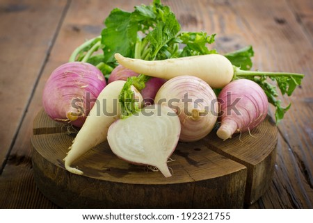 Fresh turnip and white radish on the wooden table - stock photo