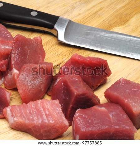 fresh uncooked beef meat sliced in cubes on board with carving knife - stock photo