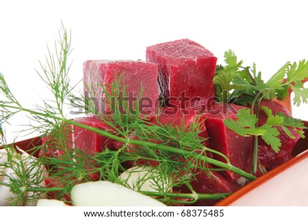 fresh uncooked beef meat slices over ceramic bowls ready to prepare with garlic and greenery isolated over white background - stock photo