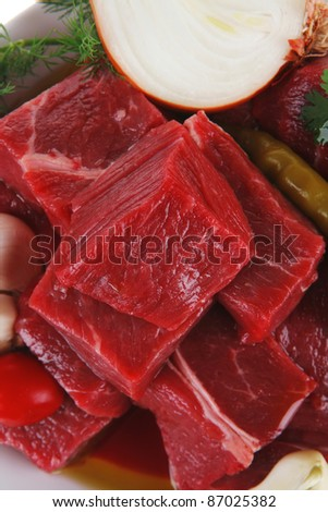 fresh uncooked beef meat slices over white bowls ready to prepare with red peppers and greenery isolated over white background - stock photo