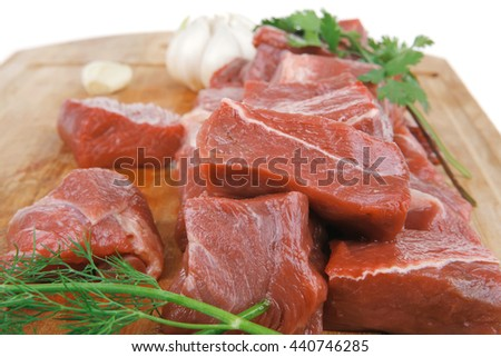 fresh uncooked beef meat slices over wooden cutting board ready to prepare with green hot and red peppers isolated over white background - stock photo