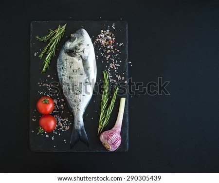 Fresh uncooked dorado or sea bream fish with vegetables, herbs and spices on black slate tray over dark grunge backdrop, top view, copy space - stock photo