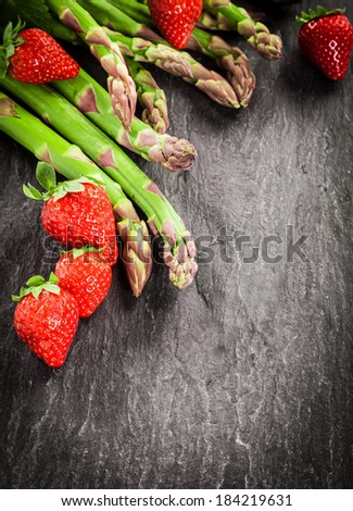 Fresh uncooked green asparagus spears and ripe red strawberries arranged as a corner decoration on textured grey slate with copyspace and vignetting - stock photo