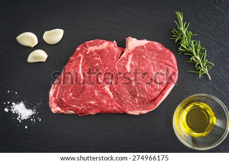Fresh uncooked rib-eye steak with garlic, salt, olive oil and rosemary on black background - stock photo
