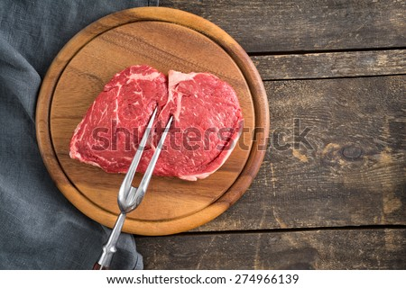Fresh uncooked rib-eye steak with large fork on wooden plate and wooden table - stock photo