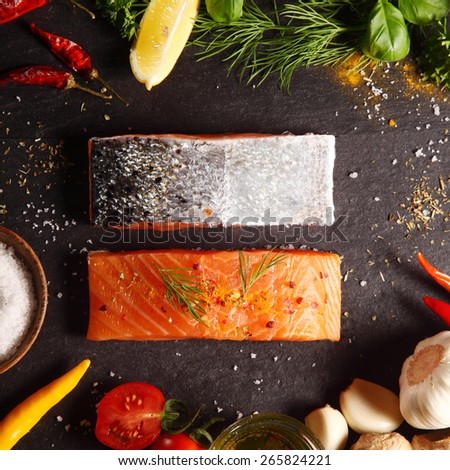 Fresh uncooked salmon fillets placed one up, one down, in a frame of ingredients for cooking the meal including tomatoes, garlic, chili peppers, herbs and seasoning, square format overhead view - stock photo